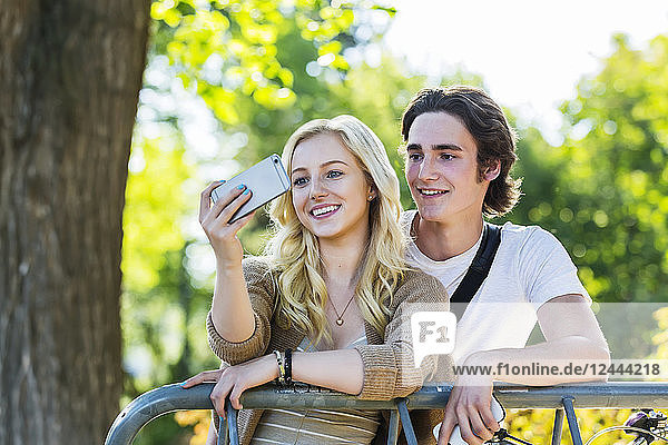 A young couple stands together at a bike rack on the university campus taking a self-portrait with a smart phone  Edmonton  Alberta  Canada