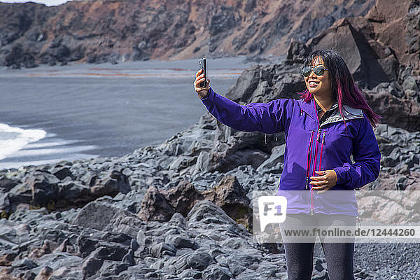 A female tourist poses for a self-portrait with her phone on the black sand beach in Western Iceland  Snaefellsnes peninsula  Iceland