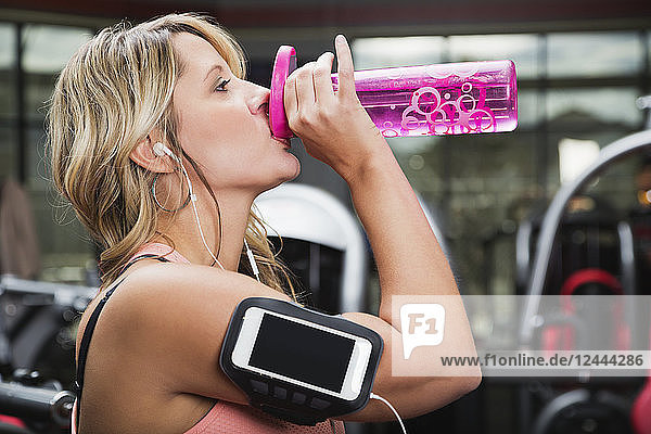 A middle-aged woman working out at a gym and drinking from a water bottle  Spruce Grove  Alberta  Canada
