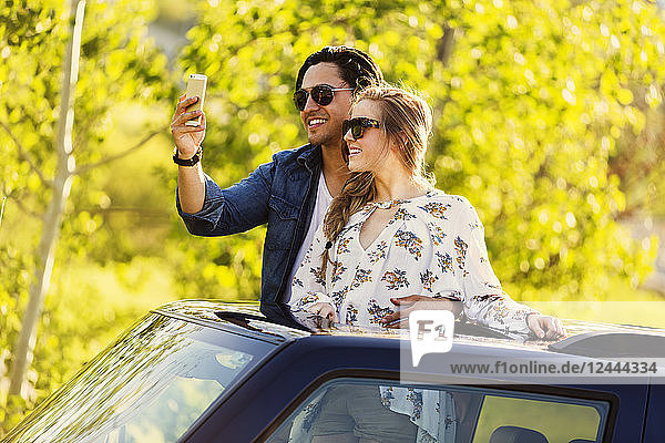 A young couple stand up through the sunroof of their vehicle and take a self-portrait with their cell phone  Edmonton  Alberta  Canada