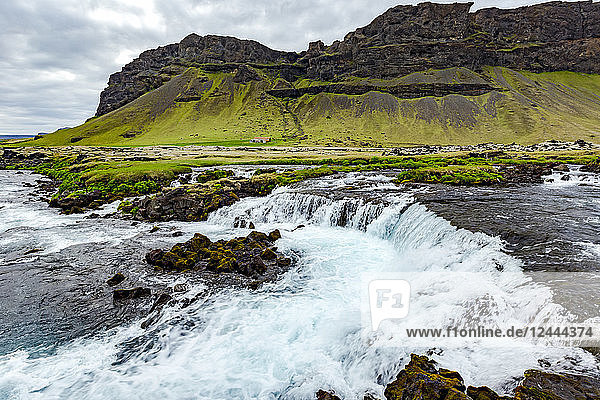 A wide angle of the river cascading over the rocks in front of a volcanic mountain and farmland  Iceland