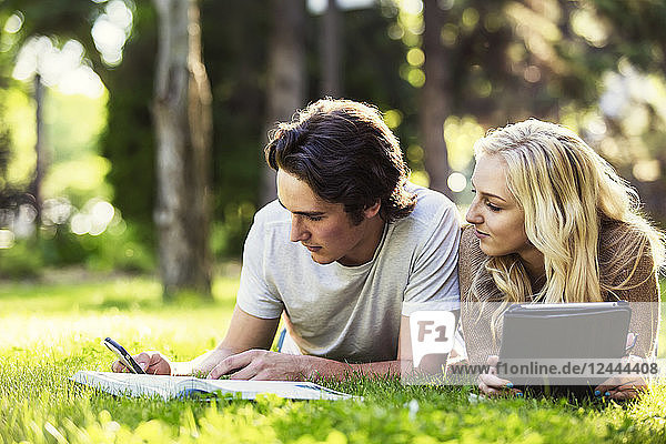 A young couple lays down studying outdoors on the grass on the university campus with a textbook and tablet and checking social media on a smart phone  Edmonton  Alberta  Canada