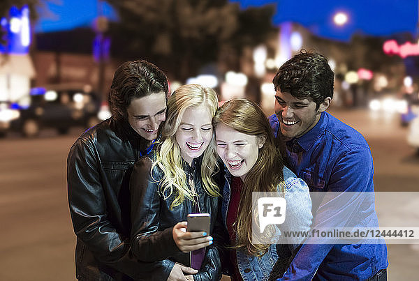 A group of four friends huddle together on a sidewalk looking at a smart phone and laughing as the glow from the screen lights up their faces  Edmonton  Alberta  Canada