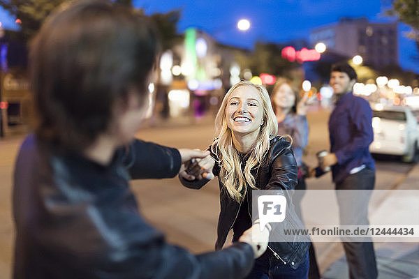 A young couple wearing black leather jackets being playful on a city sidewalk at night with friends watching in the background  Edmonton  Alberta  Canada