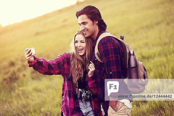 Young couple in a park posing for a self-portrait with their cell phone  Edmonton  Alberta  Canada