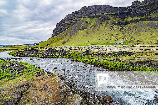 A fresh looking blue river runs along the edge of a farm property with volcanic mountains in the background  Iceland