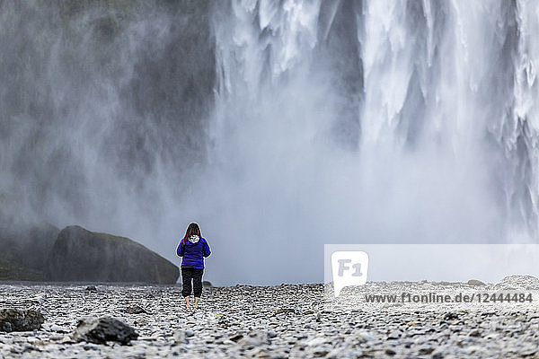 A female tourist looks towards the wall of water from Iceland's famous Skogafoss waterfall  Iceland