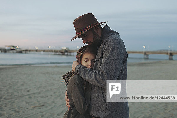 A father and daughter having a tender moment,  the father holding his daughter in an embrace on a beach at dusk; Long Beach,  California,  United States of America