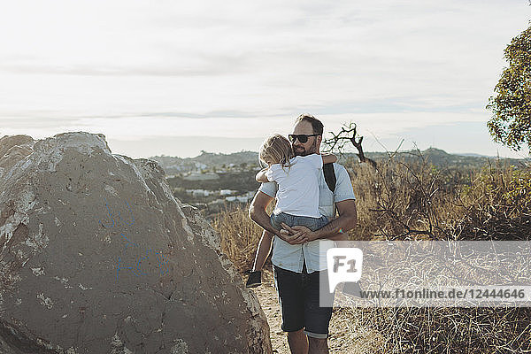 A father carries his young daughter on a hiking trail; Los Angeles  California  United States of America
