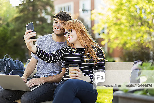 A young man and young woman sit together on a bench on the university campus taking a self-portrait on a smart phone while drinking coffee  Edmonton  Alberta  Canada