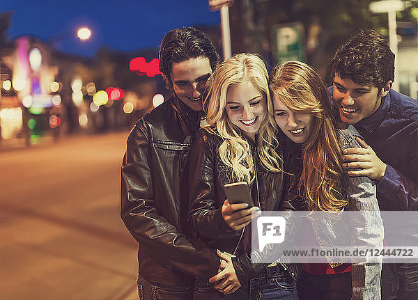 A group of four friends huddle together on a sidewalk looking at a smart phone as the glow from the screen lights up their faces  Edmonton  Alberta  Canada