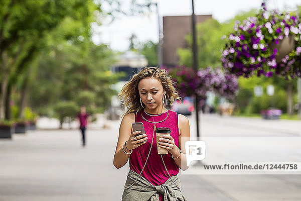 A young woman walking down a street near a university campus texting on her smart phone  Edmonton  Alberta  Canada