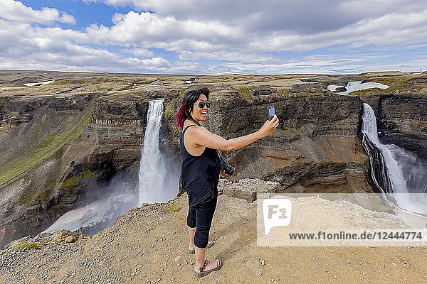 A young asian female hiker poses for a self-portrait on the edge of the Haifoss waterfall valley  a popular hiking destination in Iceland  Iceland