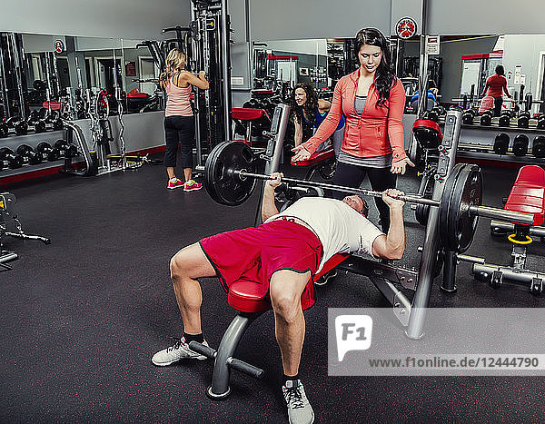 A middle-aged man doing a bench press at a fitness facility while being spotted by his personal trainer  Spruce Grove  Alberta  Canada