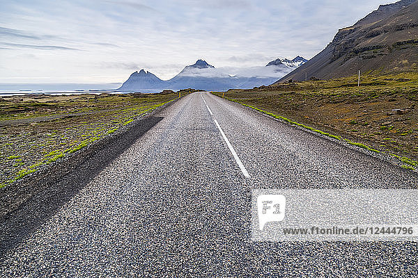 The long paved highway leading into the volcanic mountain landscape in the distance  Iceland