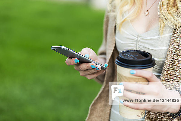 Close-up of a young woman's hands with blue fingernail polish holding a coffee cup and texting on her smart phone  Edmonton  Alberta  Canada