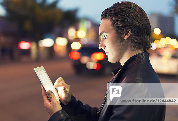 A young man uses a tablet along a street at dusk with the glowing screen illuminating his face  Edmonton  Alberta  Canada