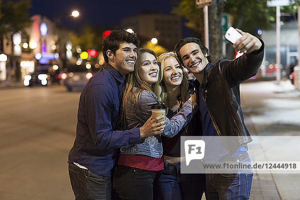 Two young couples stand closely together on the street at nighttime to pose for a self-portrait with a smart phone  Edmonton  Alberta  Canada