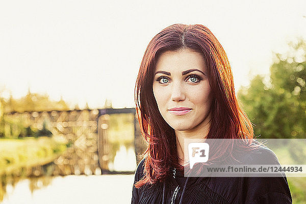 A portrait of a beautiful young woman with red hair standing on the shore of river with a historic  iconic  trestle bridge in the background  St. Albert  Alberta  Canada