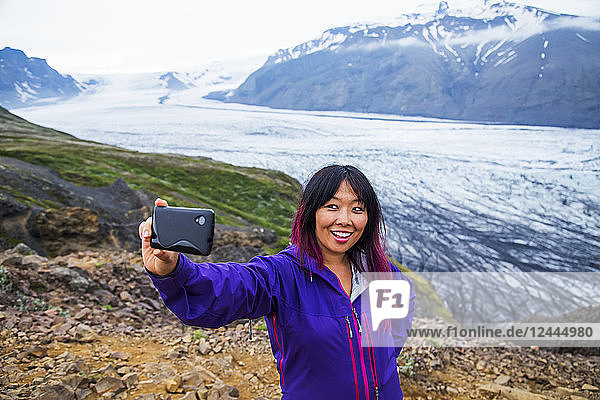 An asian female hiker takes a self-portrait from the mountain top with the glacier in the background at Vatnajokull National Park  Iceland