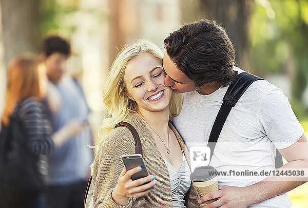 A young man kisses a young woman on the cheek while she is checking social media on a smart phone on a university campus  Edmonton  Alberta  Canada
