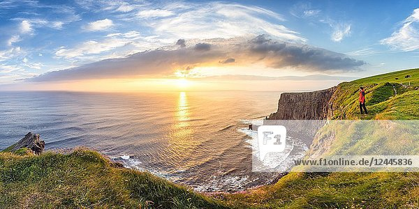 Man looking at Sunset at the Cliffs of Moher  County Clare  Munster province  Republic of Ireland  Europe.