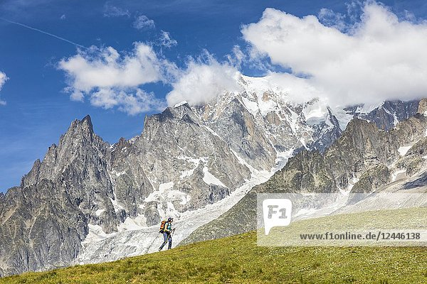 A trekker is walking in front of the Mont Blanc during the Mont Blanc hiking tours (Ferret Valley  Courmayeur  Aosta province  Aosta Valley  Italy  Europe).