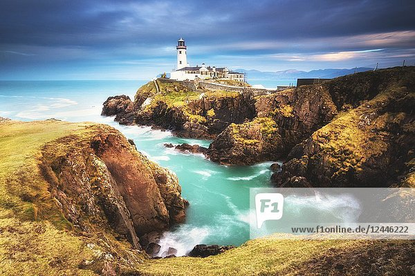 .Fanad Head (Fánaid) lighthouse  County Donegal  Ulster region  Ireland  Europe. A photographer on the field at sunrise near Fanad Head lighthouse