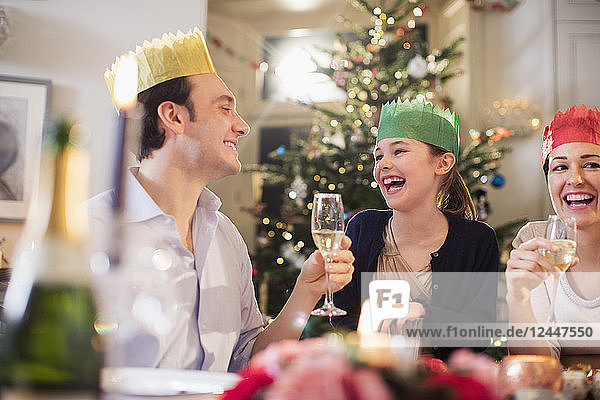 Happy family in paper crowns enjoying Christmas dinner  drinking champagne and laughing