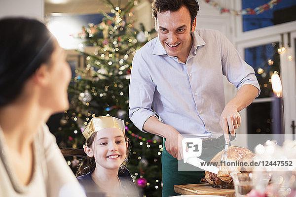 Family carving Christmas turkey  enjoying dinner
