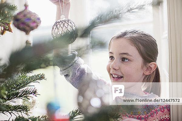 Girl decorating  hanging ornament on Christmas tree