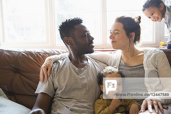 Affectionate multi-ethnic young family on living room sofa