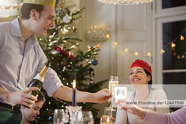 Happy man serving champagne at candlelight Christmas dinner