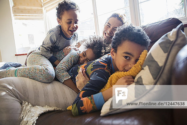 Portrait happy mother and children cuddling on living room sofa