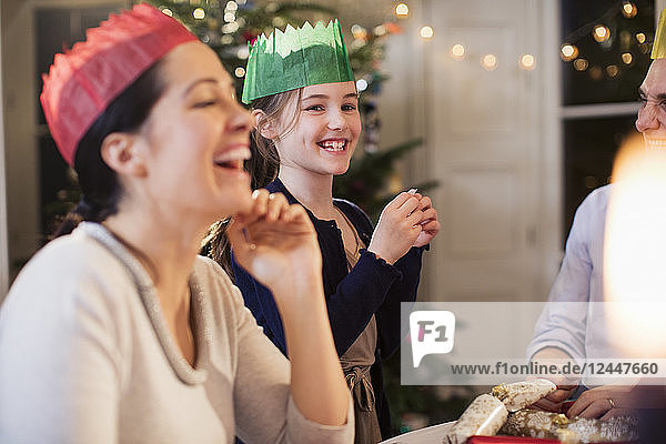 Happy family in paper crowns laughing at Christmas dinner