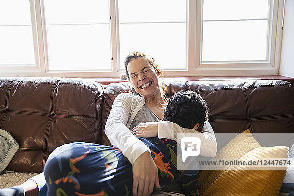Happy  carefree mother cuddling with son on living room sofa