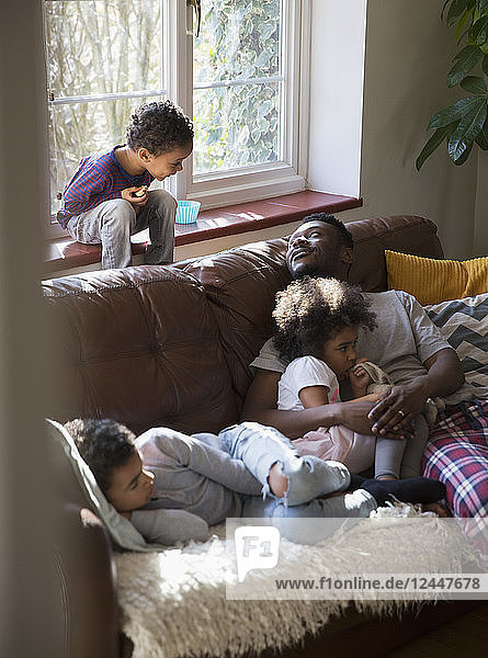 Father and children relaxing  cuddling on living room sofa
