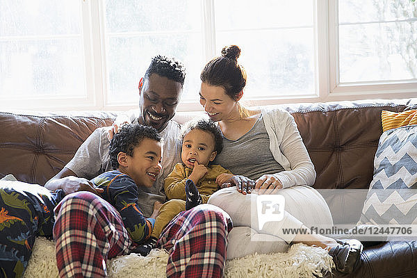 Multi-ethnic young family relaxing in pajamas on living room sofa