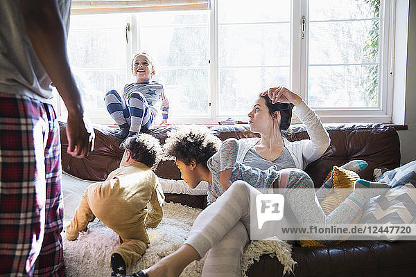 Multi-ethnic young family in pajamas playing in sunny living room
