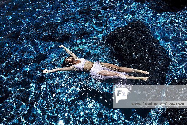 Greece  Crete  Chersonissos  woman floating in lagoon  wearing dress