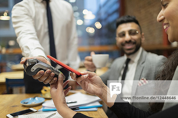 Businesswoman paying with smart phone contactless payment in cafe