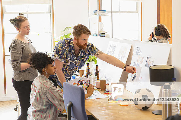 Creative designers reviewing story board proofs in office