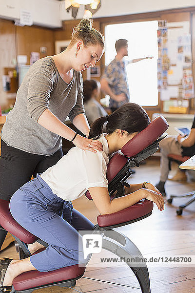 Creative businesswoman receiving massage from masseuse in office