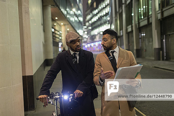 Businessmen with bicycle and paperwork walking on urban sidewalk