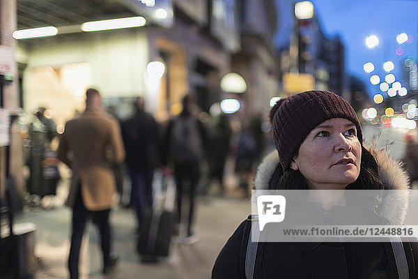 Woman in warm clothing standing on urban sidewalk at night Woman in warm clothing standing on urban sidewalk at night