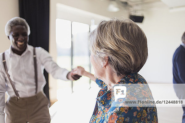 Active senior couple dancing in dance class
