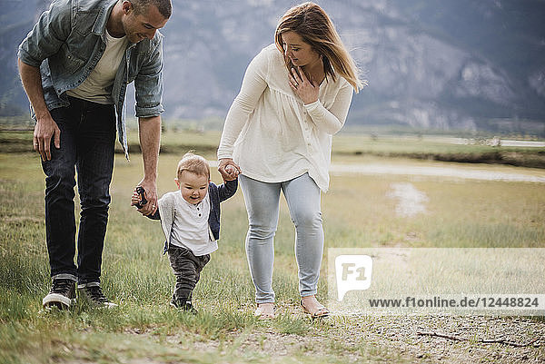 Parents walking with baby son in rural field