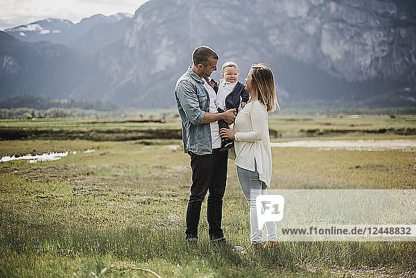 Parents and baby son standing in rural field
