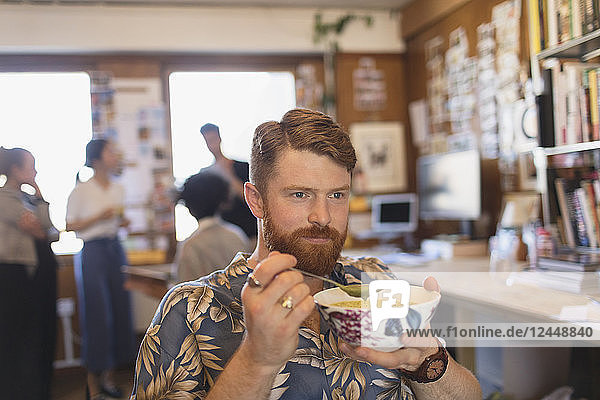 Creative businessman eating soup in office