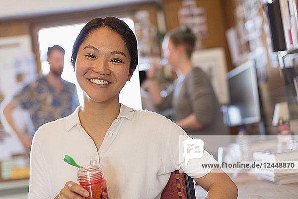 Portrait smiling creative businesswoman drinking juice in office